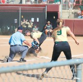 Third baseman Sydney Biggs (center) tags out the advancing Lady Lion runner for the first out in the fourth inning. Abby Hutchens (#9) backs up third base.