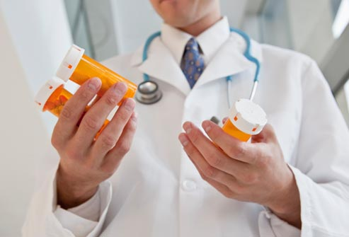 getty_rf_photo_of_doctor_holding_pill_bottles