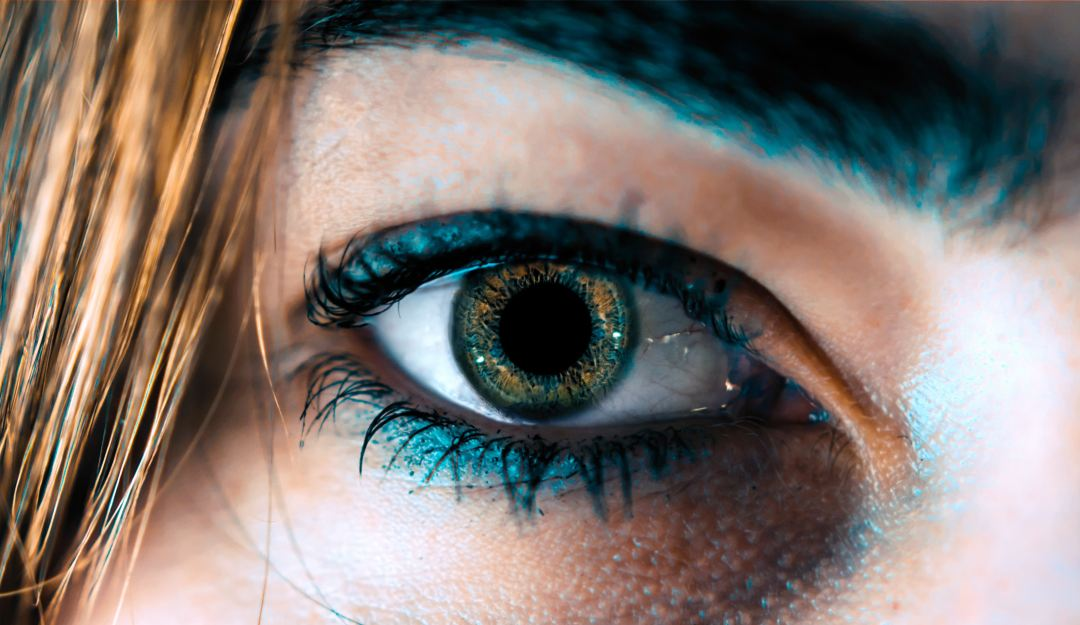 Close up of a womans eye with green make up.