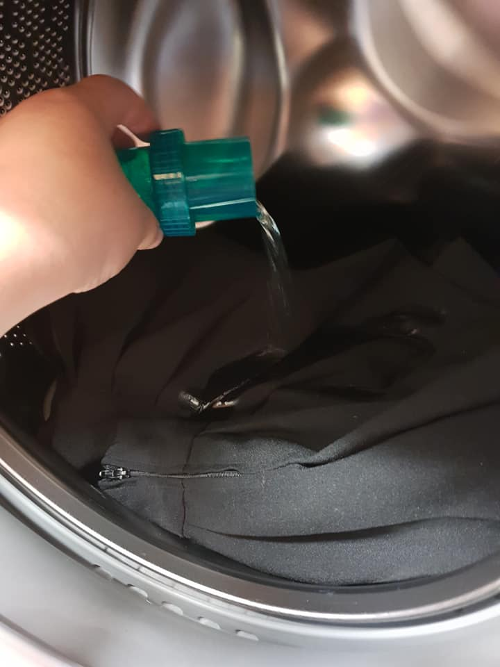 pouring ace in the washing machine