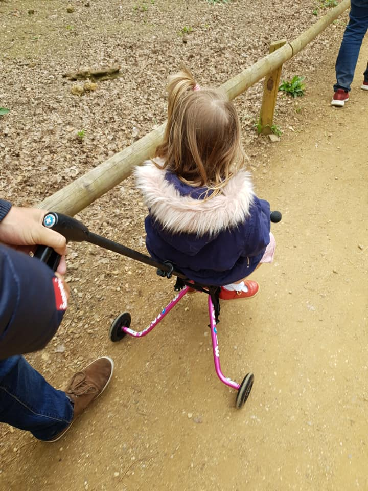 Shaniah is sat on the micro trike as we walk around Cotswold Wildlife Park's grounds.