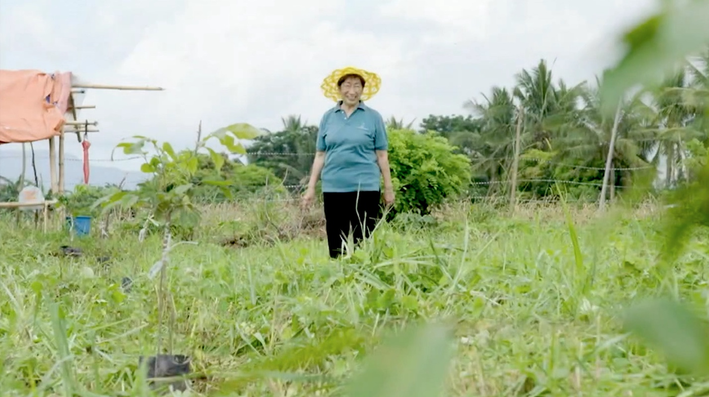 Rosalina standing in her field at the The Happy Pili Tree Farm