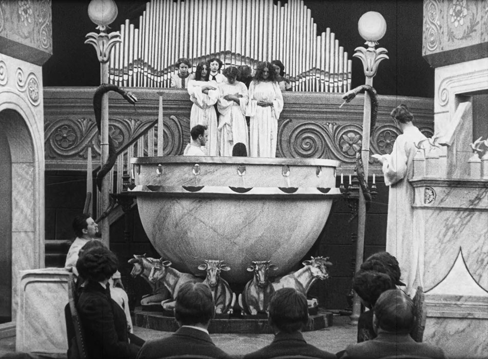 A man is baptizing a woman in a depiction, from A Victim of the Mormons (1911), in a replicated Salt Lake Temple.