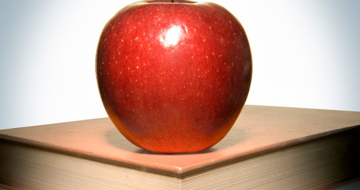 Shiny red apple sitting on top of a book