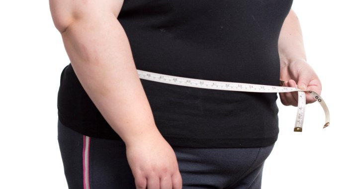 overweight woman measuring waistline with tape measure