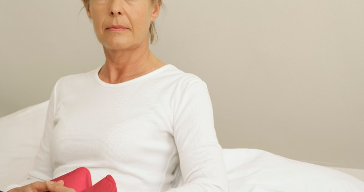 Mature woman holding hot water bottle over her stomach