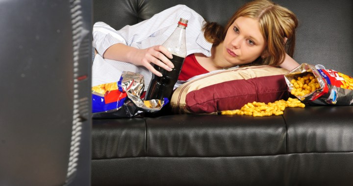 bored woman on couch eating chips and soda