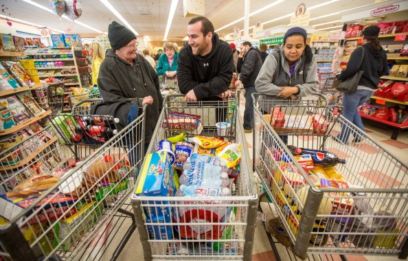 People fill their grocery shopping carts with foods they like.