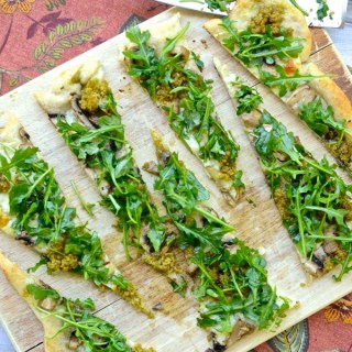 This recipe for Mushroom Pesto Arugula Flatbread takes just 20 minutes if you use a Pillsbury Crust, which means you can have a light spring dinner on the table any night of the week! It's so delicious, you'll still devour it in half the time it took to make. | theeverykitchen.com