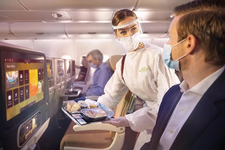Etihad cabin cabin crew with guest wearing face masks