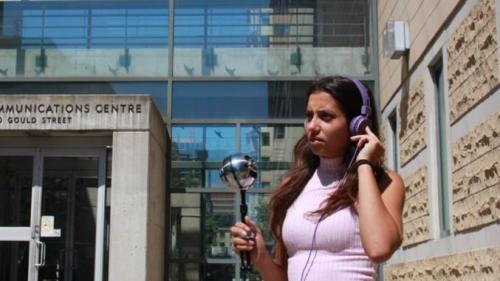 A student wearing headphones and holding a mic, stands outside the RCC.