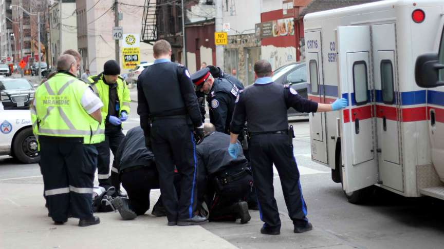 A group of police officers and emergency responders surround a man on the ground, seemingly waiting to escort him into their vehicle