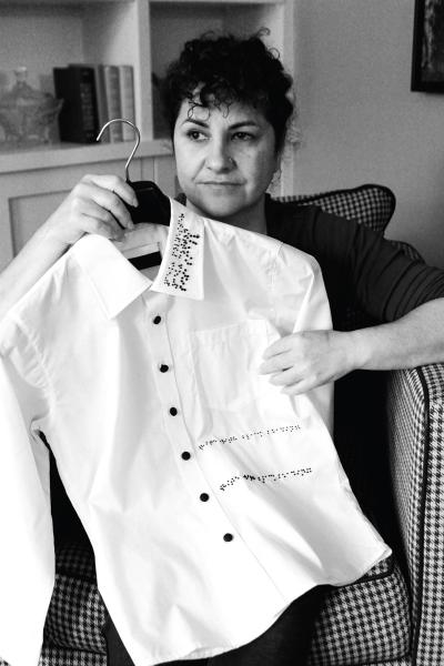A woman holding a shirt with a braille design on it.