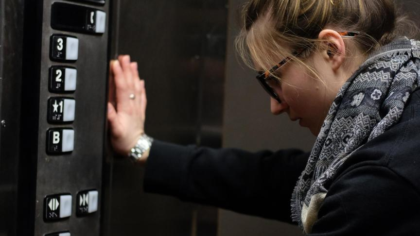 A student stands with their hand pressed against the side of an elevator, looking sadly at the buttons.