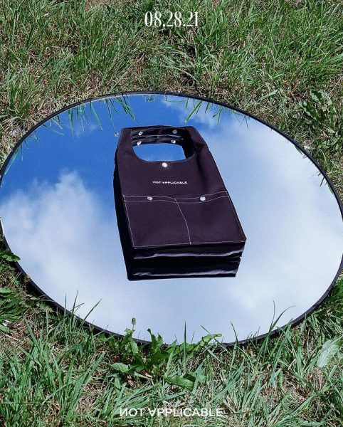 A plain black tote bag on a mirror placed on grass while its facing the sky