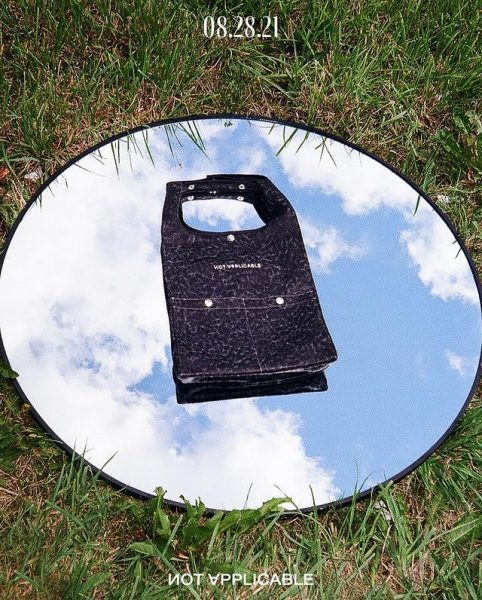 A black tote bag with white details on a mirror placed on grass while its facing the sky