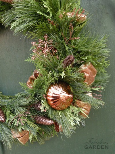 close up of wreath decorated in bronze accents