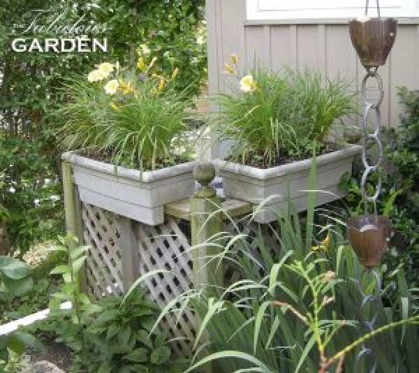 lattice screening boxes in an air conditioning unit, with planters of daylilies rimming the edge