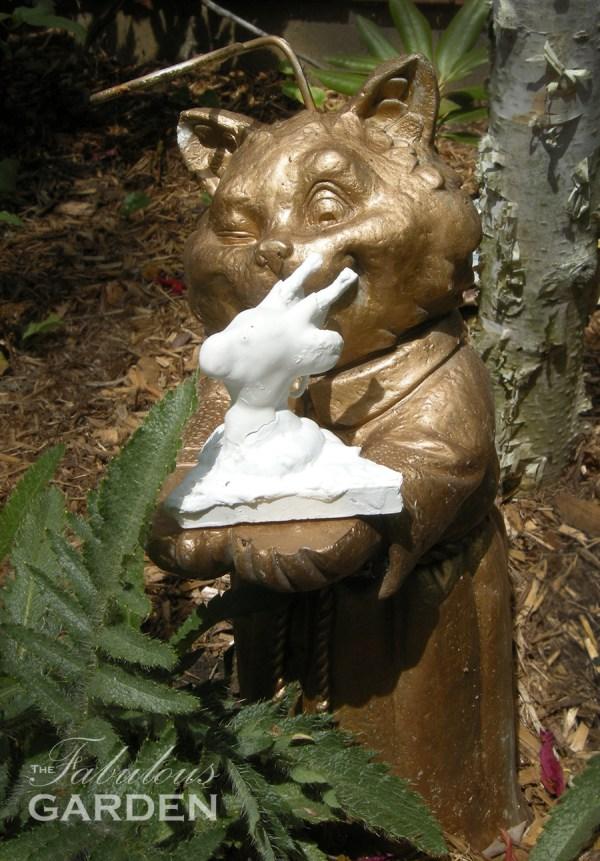 gold cat statue eyeing a ceramic bird