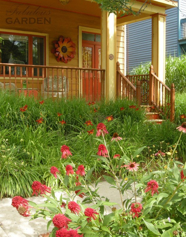 House painted in shades of orange is set off by the hot coloured plantings in front