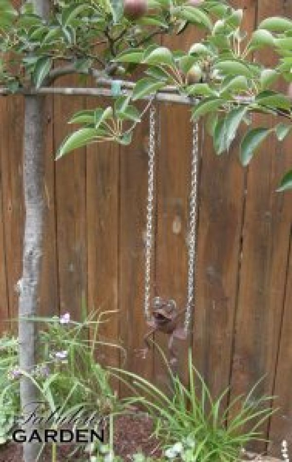 Metal frog swings from a pear tree limb