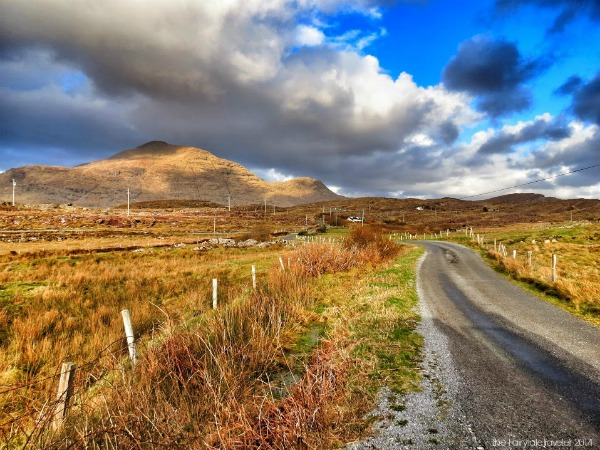 Driving along the Wild Atlantic Way in the Connemara region. Here the mountain peaks are many and the valleys are deep. This coastal road hugs craggy cliffs and sandy shores, and it never gets old.