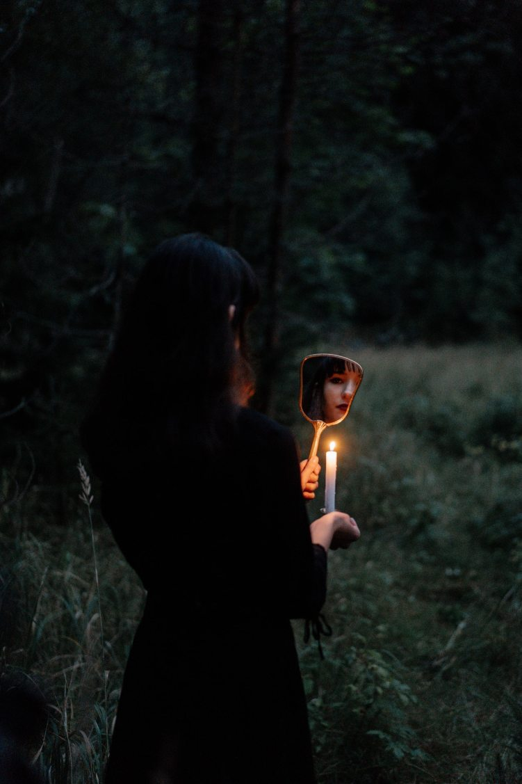 witch trials UK woman with candle and mirror dark