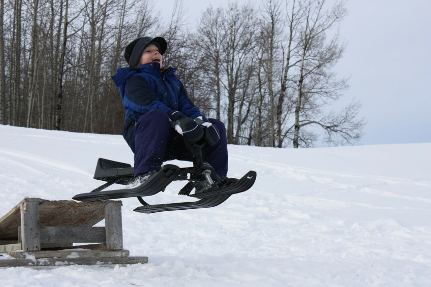 Montreal winter activities, boy riding sleigh