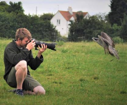 boy with photo camera photographing a falcon at The Falconry School