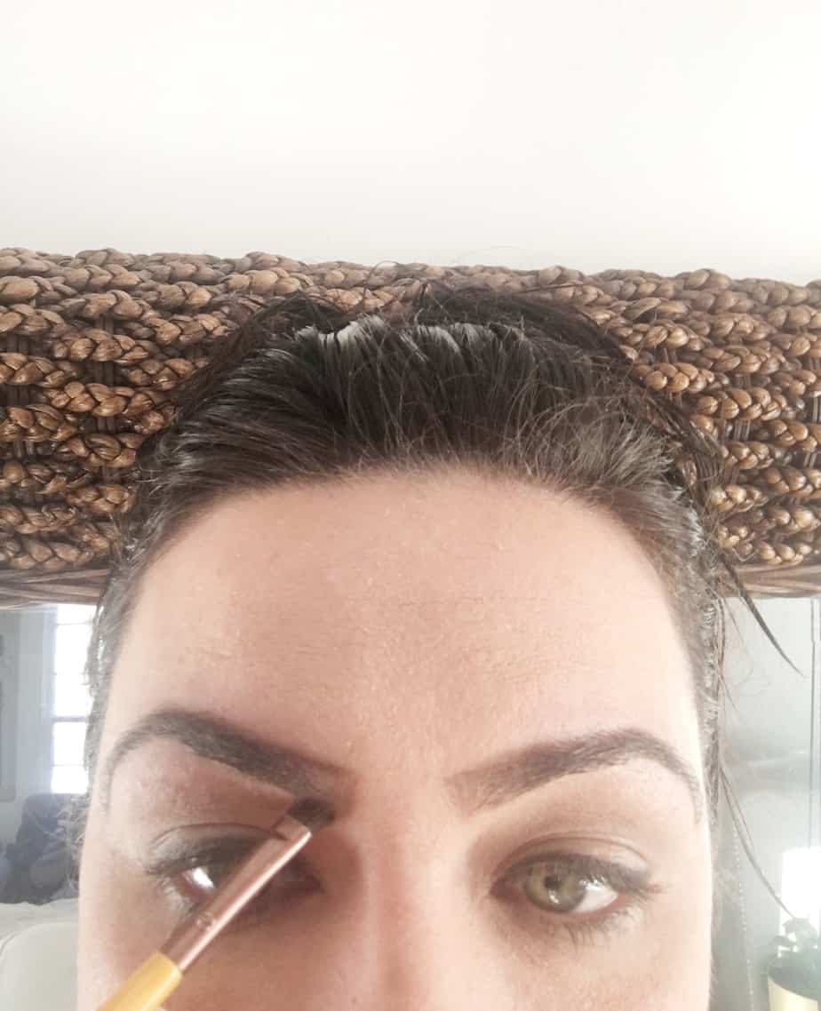 A woman shaping her brows.