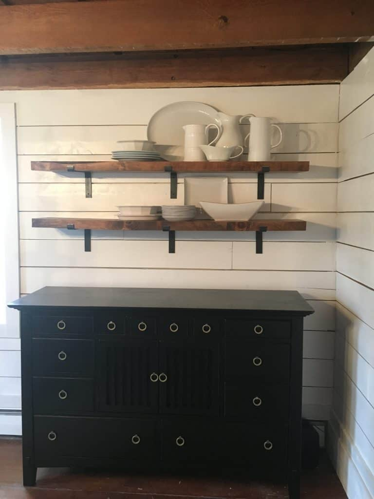 White plates, bowls, and pitcher on the shelves.