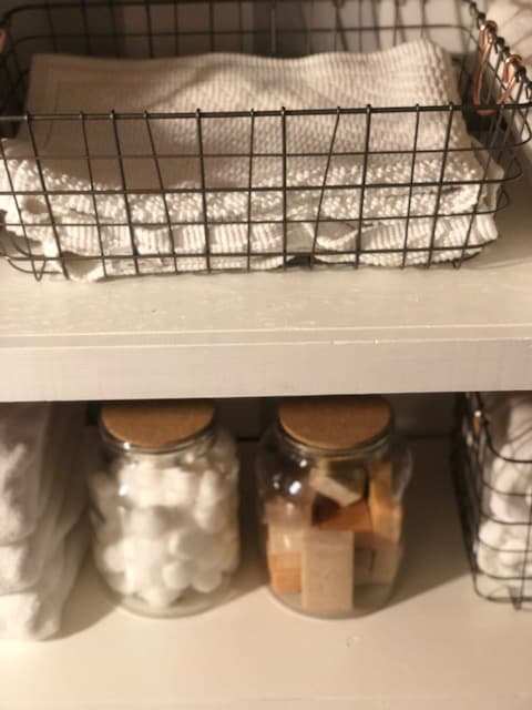 A wire basket with towels in it.