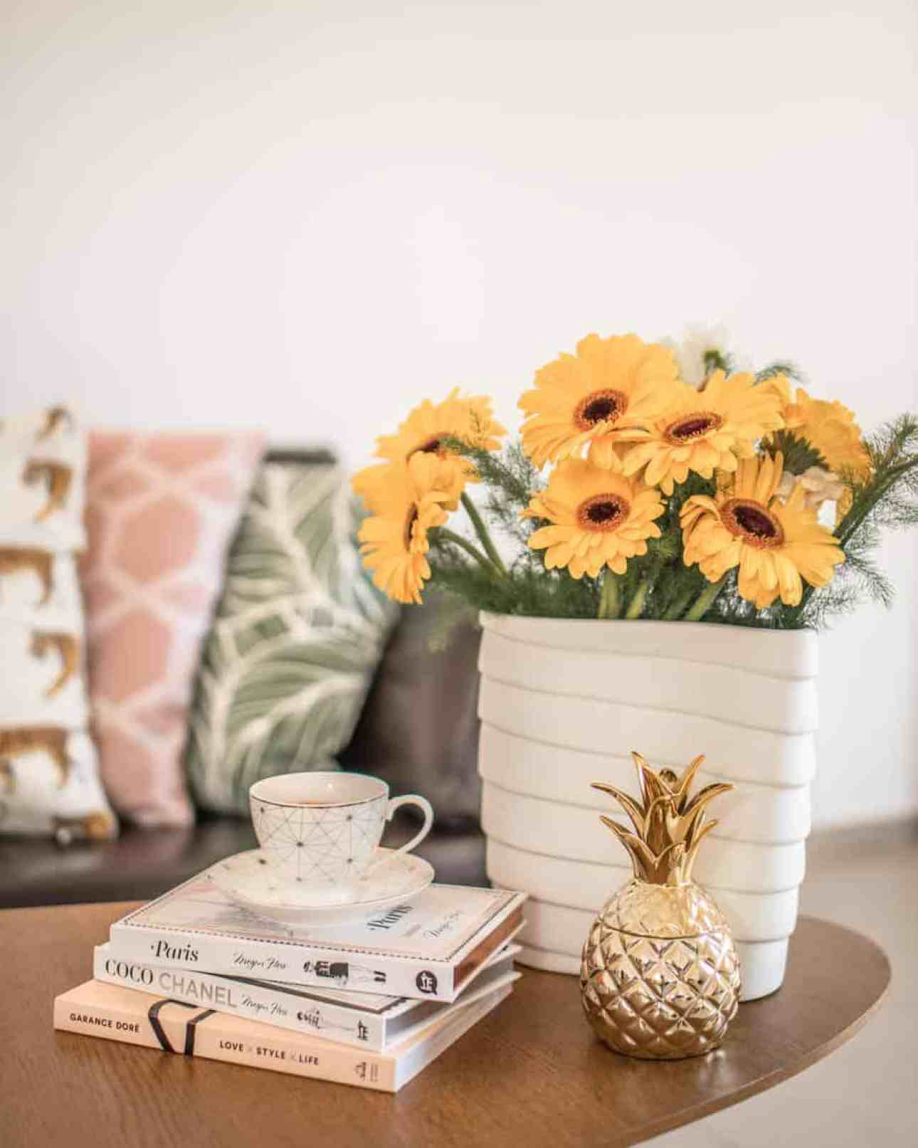 Yellow flowers in a white vase on the coffee table.