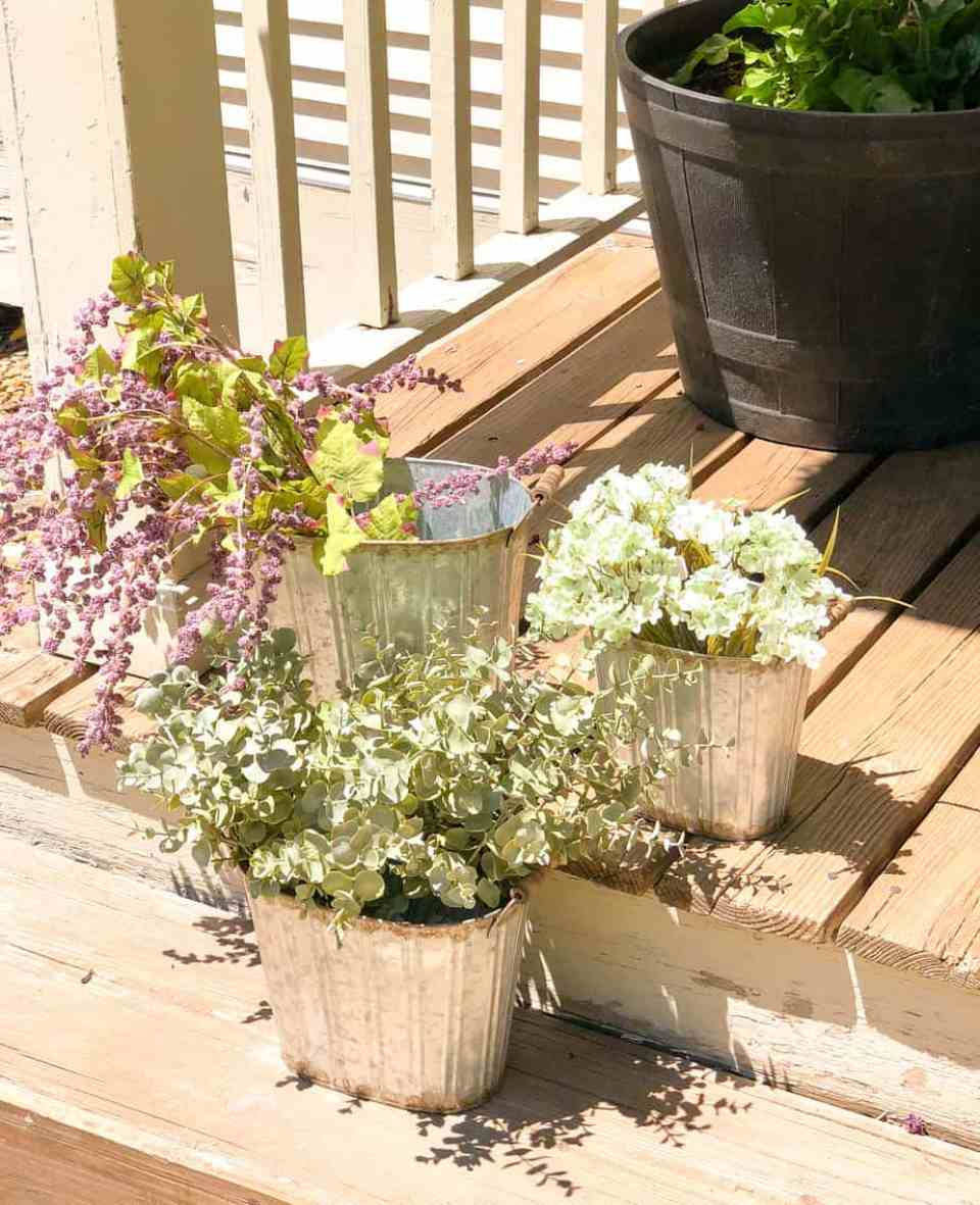 Three buckets on the porch filled with flowers.