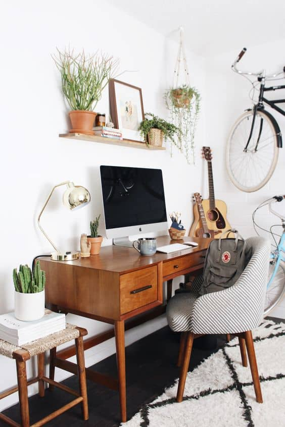A wooden desk with a guitar in the corner and a bicycle.