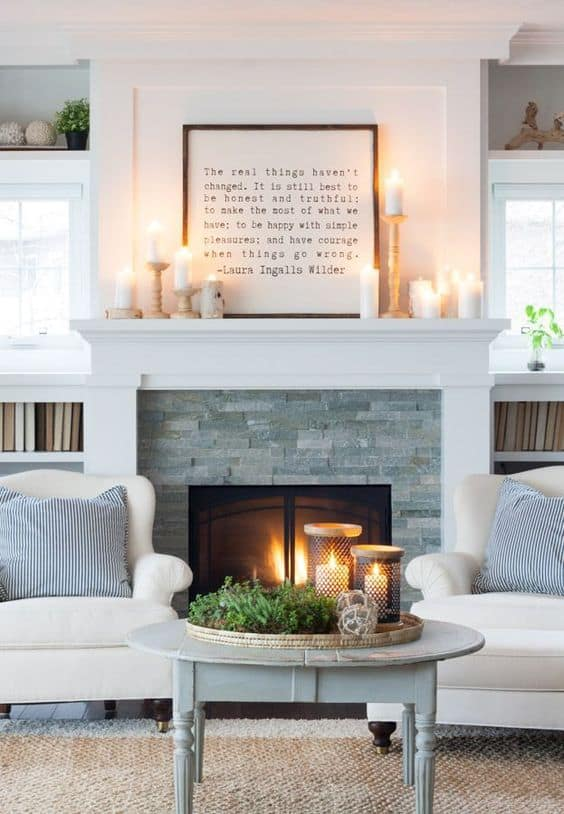 A stone and white mantel with a framed graphic quote on top of the mantel.