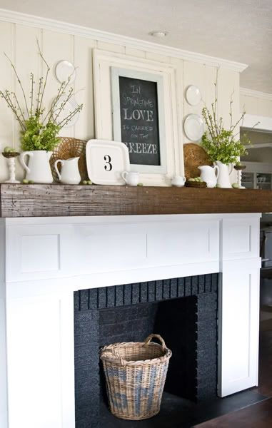 A wooden and white fireplace with a chalkboard framed and a graphic on it.   There is a wicker basket in the fireplace.