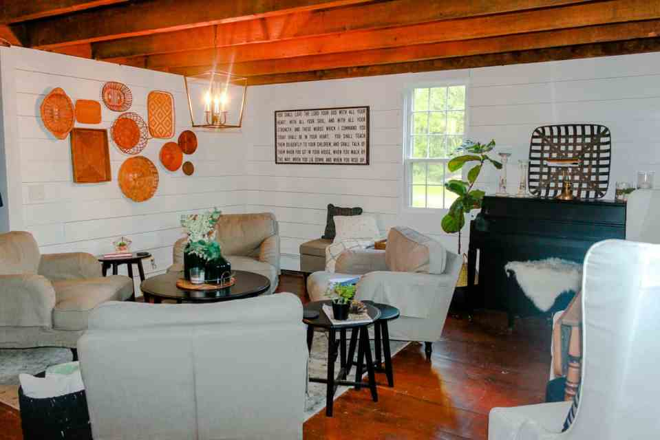 The sitting room with the basket wall, neutral couches and wood beams on the ceiling.