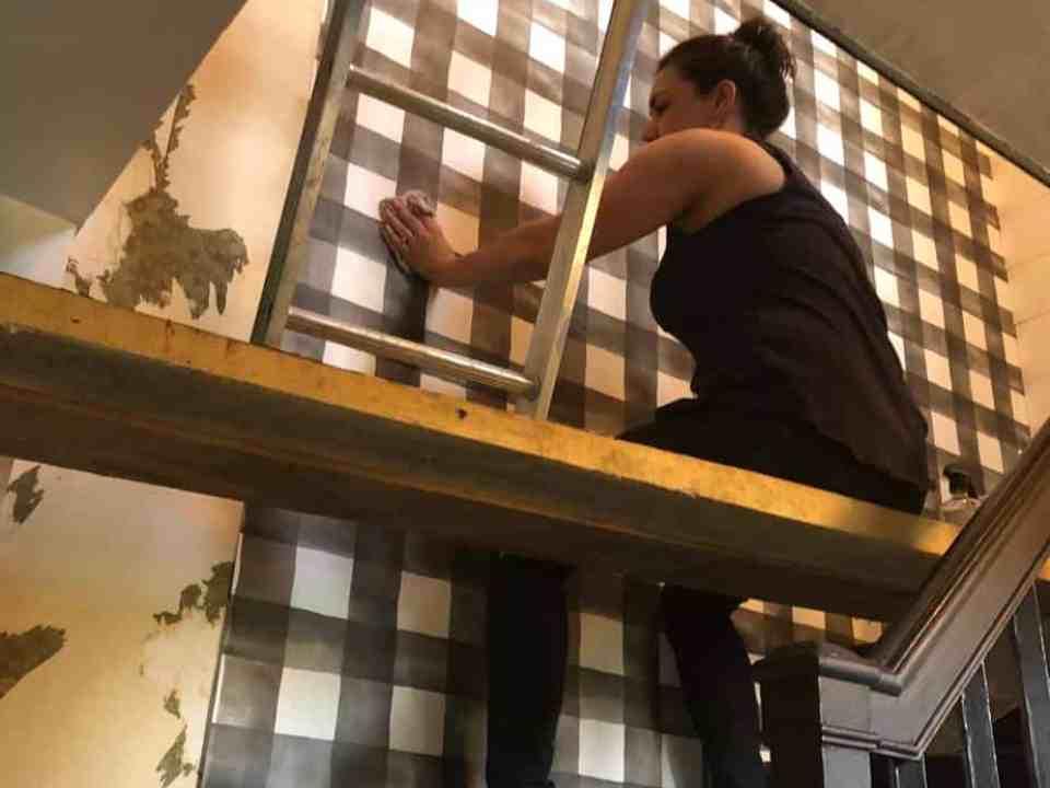 Kori on a platform putting up the wallpaper.