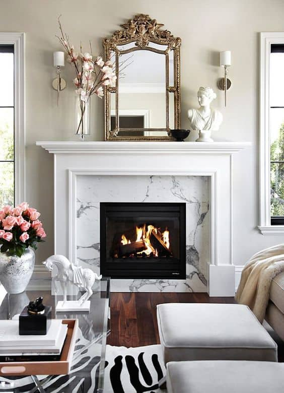 White and marble fireplace with a French inspired mirror above it, and wall sconces flanking the mirror.