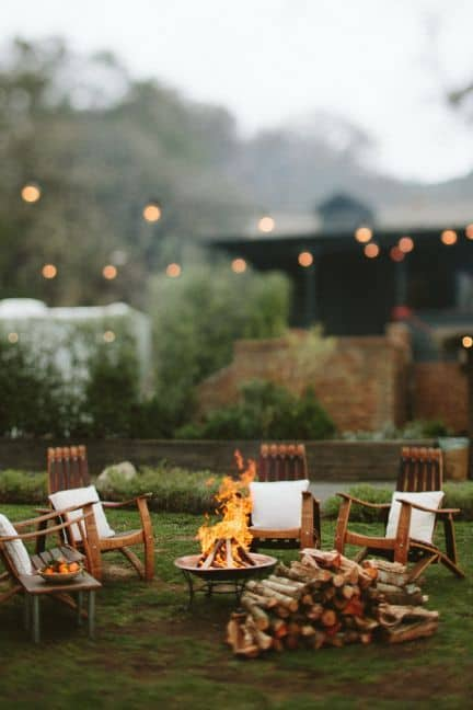 A backyard fire pit with wooden chairs around the fire, there are neutral cushions on the chairs.   There is also a a stack of logs beside the fire pit.