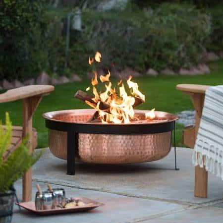 A copper bowl fire pit on a cement patio in the backyard.