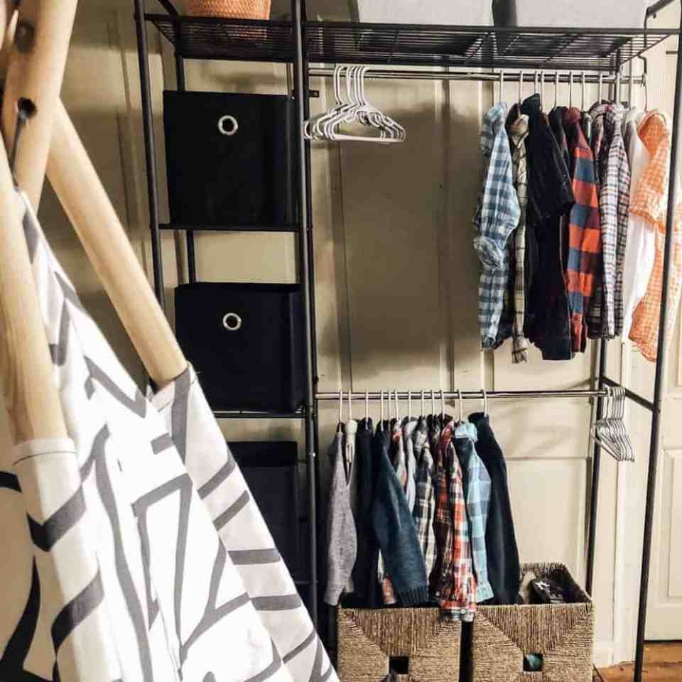 A metal rack wardrobe with clothes hanging in it, and bins for shoes in the wardrobe.