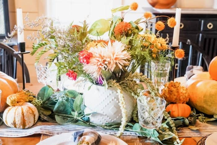 The floral centerpiece with pumpkins, and a striped table runner.