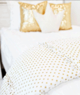 White bedding with gold pillows.