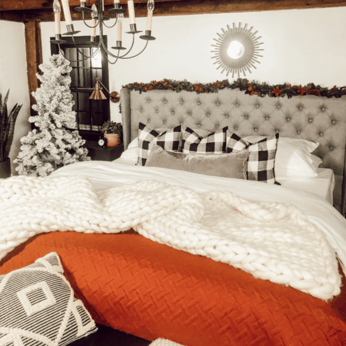 Bed with red blanket and a flocked Christmas tree in the corner of the room.