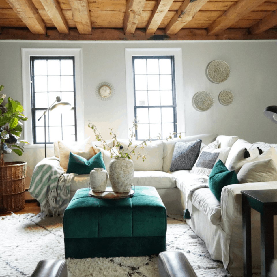 A white couch and wood beam ceiling.