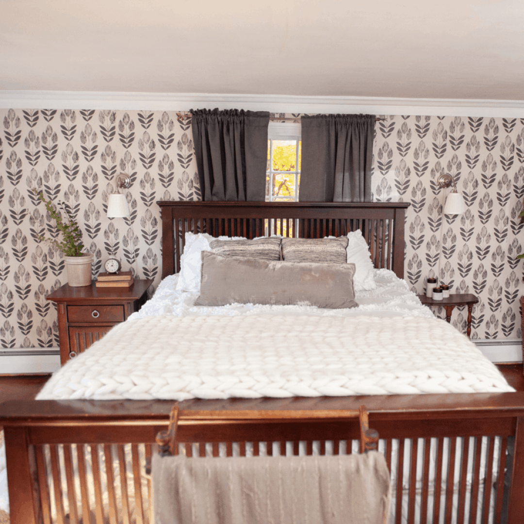 Bed with white bedding an gray throw pillows.