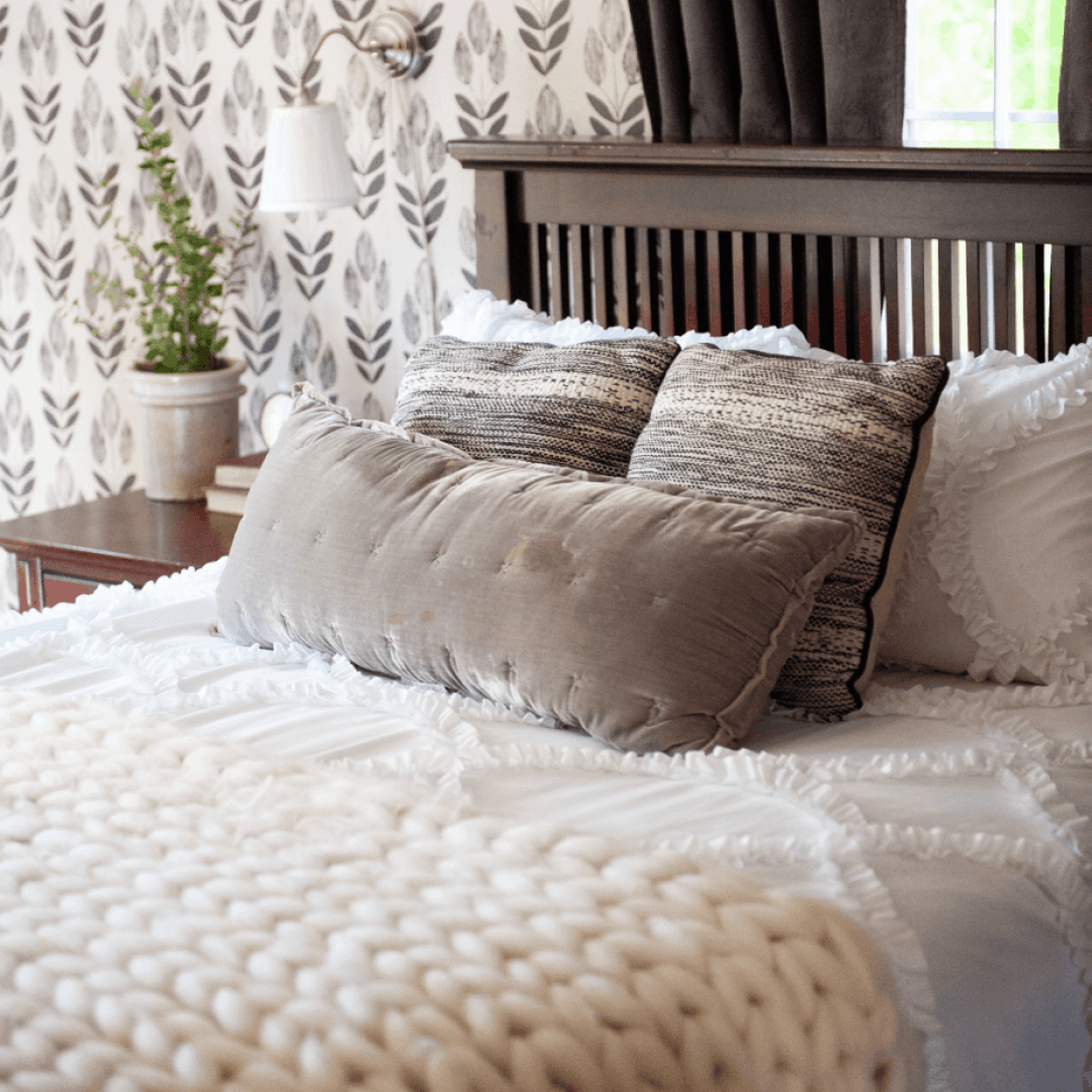 Cozy bed with white blankets and throws pillows.