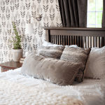 white knitted blanket on a bed with gray pillows Scandinavian wall paper and gray curtains